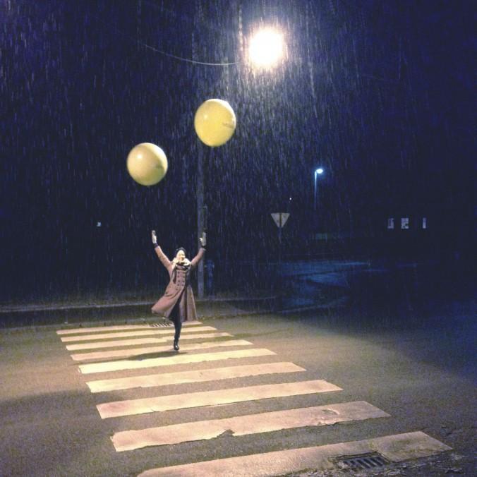 Frau in Mantel mit zwei großen schwebenden Luftballoons in Baumpose steht auf Zebrastreifen. Es regnet und schaut mystisch aus