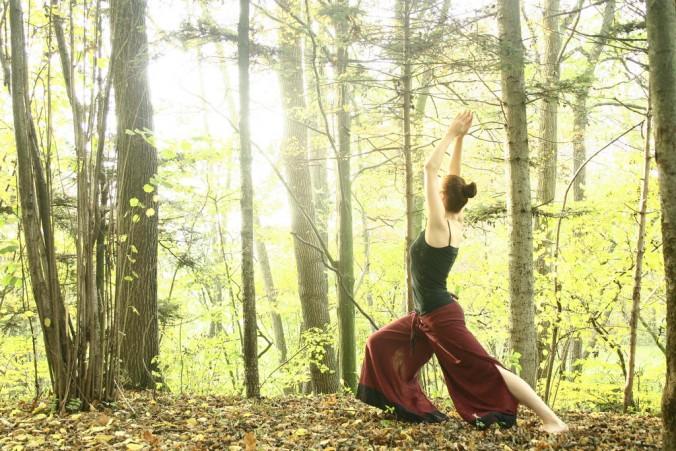 eine Frau steht in der Heldenhaltung auf einer Anhöhe im Wald, ihre Hände gefalten nach oben gestreckt. Zwischen den Bäumen strahlt Licht. Sie richtet ihren Blick zum Licht. Eine friedvolle, kräftige, lebendige Atmosphäre entsteht.