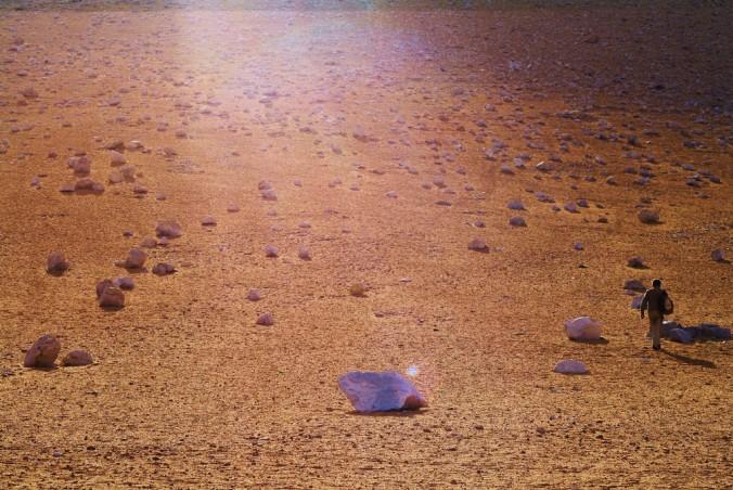 ein mann wandert durch eine steinwüste, ein sonnenstrahl erhellt das in blau-gold gehaltene bild