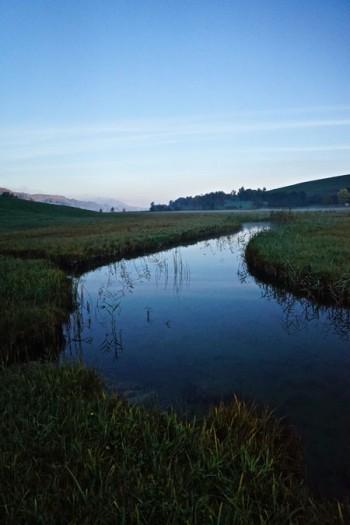 ruhiger Fluss mit glatter Oberfläche am Morgen, eingebettet in mossgrünes Gras; im Hintergrund ein Berg. Der Fluss mündet in einen See; im Wasser spiegeln sich die Gräser