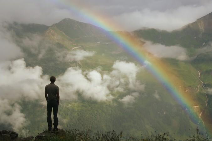 Regenbogen am Berg, ein Mann von Hinten schaut nach vorne, gegenüber ein Berg, Wolken ziehen vorüber