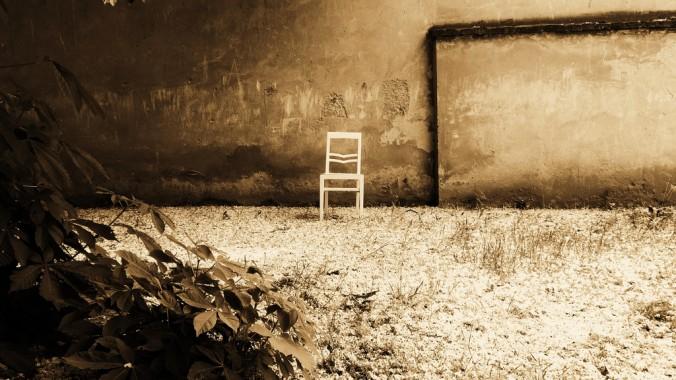 weißer Sessel in einem Hinterhof in Wien; am Boden ein Blütenmeer eines Kastanienbaums, grauer Hintergrund
